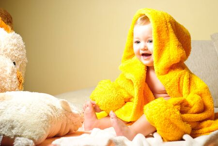 after the bath: Girl after bathing, sitting in yellow bathrobe Stock Photo