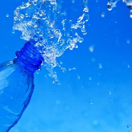 aqua background: agua Splash de botella en azul Foto de archivo