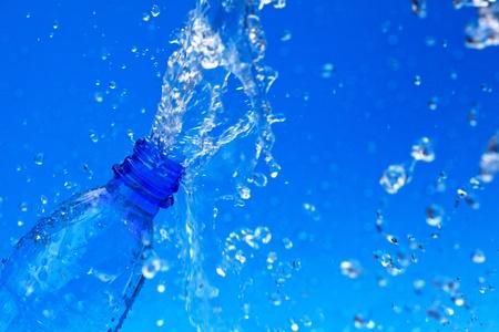 splash water from bottle on blue photo