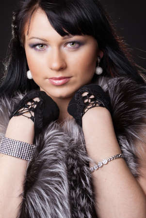 Woman in fur coat on black backgound Stock Photo - 9619307
