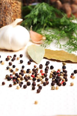 peppercorns: Different peppercorns on white napkin and spices Stock Photo