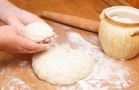 haciendo pan: Harina en capacidad con masa y rodillo sobre la mesa de madera