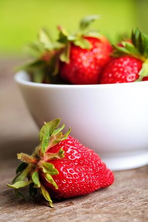 Strawberry with bowl on wooden table outdoor