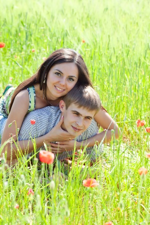 Couple in poppy field,  lying down, close up faces Stock Photo - 9800735