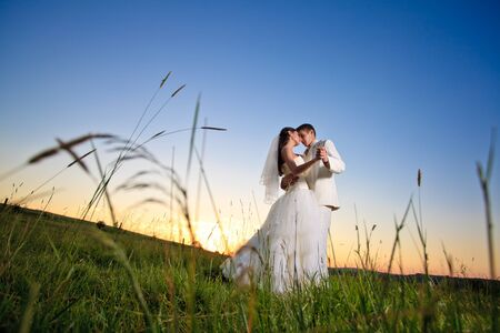 Wedding couple dansing in mountain hill on sunset photo