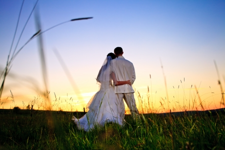 people from behind: Wedding couple looking in mountain hill on sunset Stock Photo