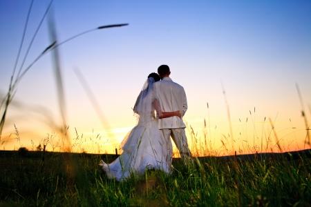 Bruidspaar op zoek in berg heuvel op zonsondergang
