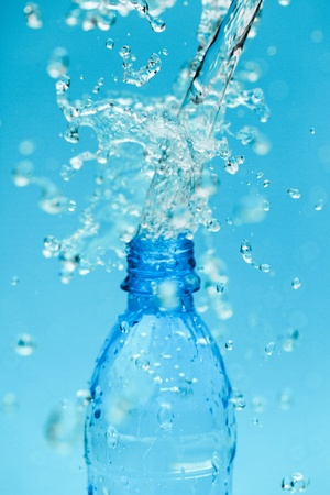splash water from bottle on blue photo