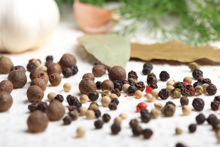 Different peppercorns on white napkin close up Stock Photo - 9970055
