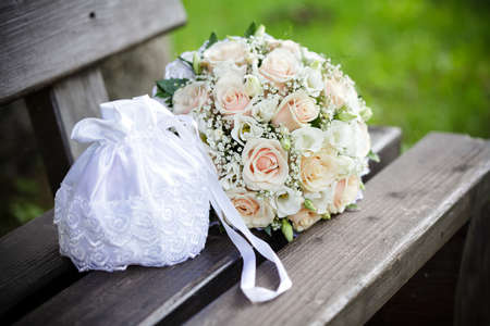 Wedding bouquet from pink roses and handbag photo