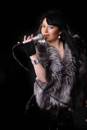 Woman singer in fur coat on black backgound photo