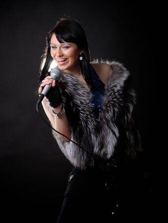 Woman singer in fur coat on black backgound Stock Photo - 10093171