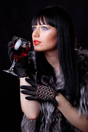 Woman with glass of red wine on black photo