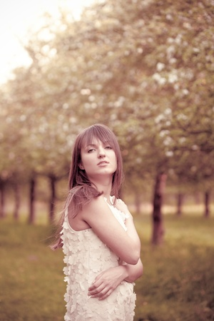 Young attractive girl in the garden. Toned in pink Stock Photo - 10093204
