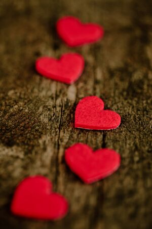 Red hearts stickers on wooden background in line, shallow DOF photo