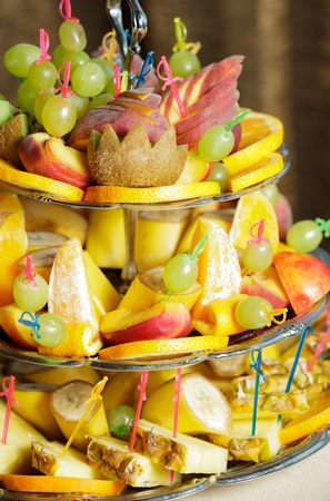 Various slices of fruits on the silver stand prepared for eating photo