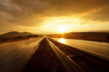 empty street: Wet road after rain and sunset over fields Stock Photo