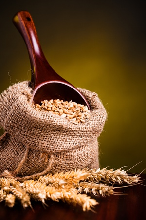 Wheat in small burlap sack and wooden spoon  photo