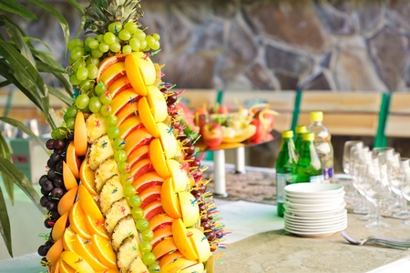 Various slices of fruits on the silver stand prepared for eating decored like form of pineapple photo