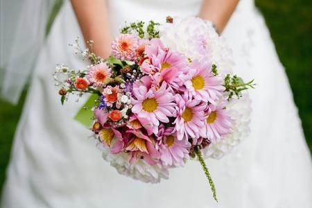 flor silvestre: La novia con un ramo de boda cerca al aire libre. Profundidad superficial del campo