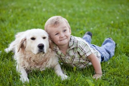 blonde boy: Cute toddler blonde boy with golden retriever hugging close up Stock Photo