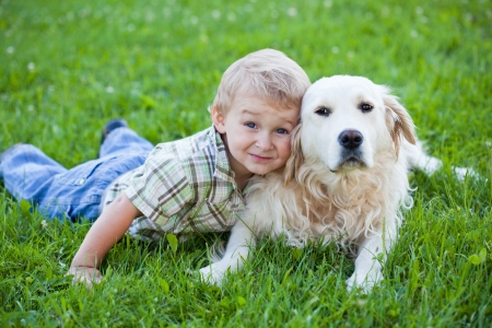 dog park: Cute toddler blonde boy with golden retriever hugging close up Stock Photo