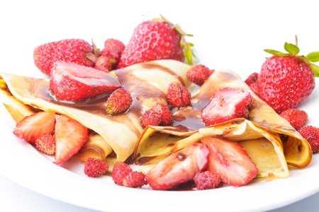 Pancakes with different strawberries with chocolate syrup on white photo