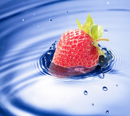 Blue water drop closeup with strawberry incide