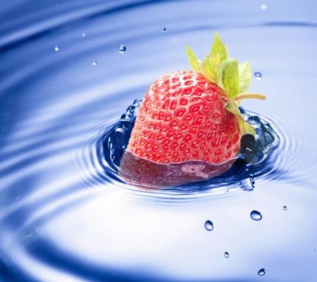 Closeup de gota de agua azul con fresa priman