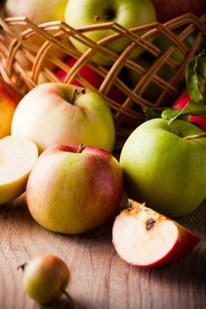 Fresh various apples closeup on wooden table photo