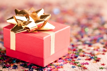 Small red gift box closeup with gold bow special for jewelery