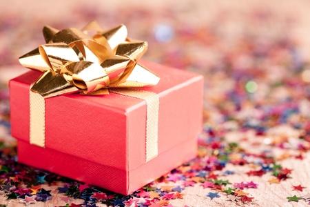 fiocco oro: Piccolo regalo rosso scatola closeup con fiocco oro speciale per gioielli