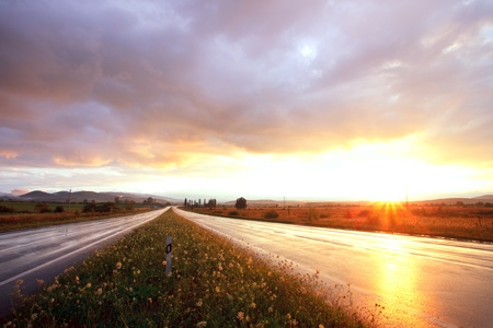 Wet road after rain and sunset over fields Stock Photo - 10432504