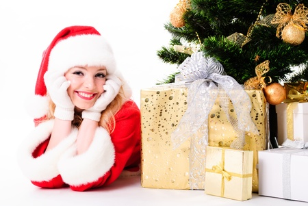 solemnity: cheerful santa girl stand near the gift and New-years tree. Christmas greetings card