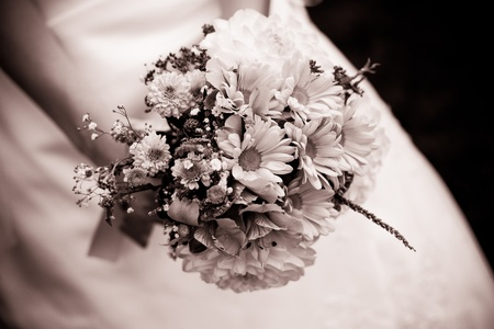 The bride with a wedding bouquet close up outdoor. Shallow deep of field, chocolate tonning