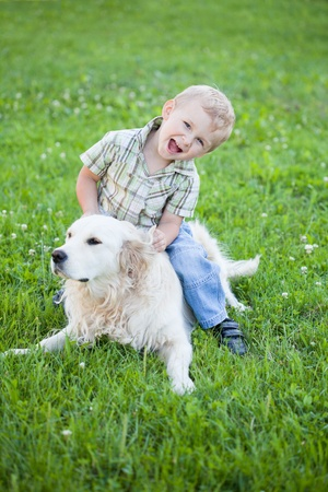 summer dog: Cute toddler blonde boy with golden retriever hugging close up Stock Photo