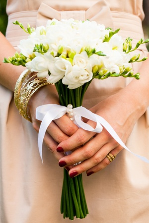 Wedding bouquet from white freesias closeup in brides hands photo