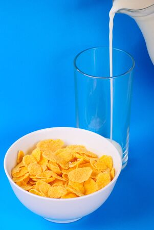 Breakfast from pouring milk and cornflakes over blue background photo