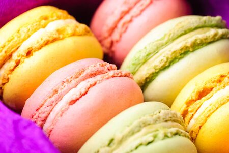 Macaroons in row close up in box photo