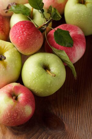 Different apples on wooden table in garden photo