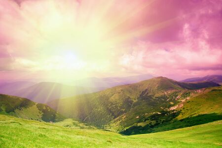 evening glow: Beautiful evening sky and green hills high up in Carpathian mountains Stock Photo