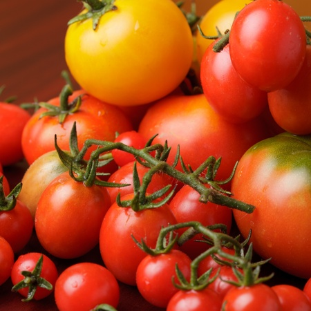 Various types of tomatoes on wooden background photo