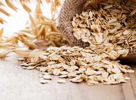 oats: Oat flakes spilling from the burlap bag on wooden table