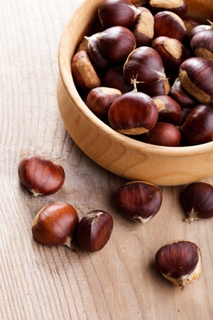 Chestnuts in wooden plate on talbe photo