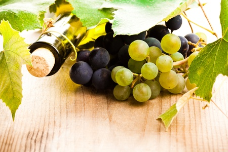 bottle of wine with leaves and grapes on wooden table photo