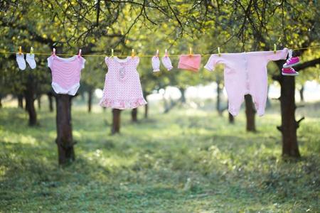 Rose vêtements pour bébés en plein air dans le jardin Banque d'images
