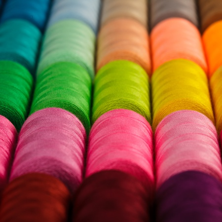 Sewing threads multicolored background closeup photo
