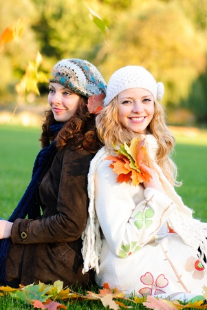 Two girl under the maple tree look on falling leaves photo