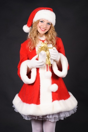 Christmas santa girl with gift isolated on black. Copy text. Christmas greetings card photo