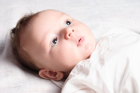 swaddling clothes: Baby boy lie on white diaper and look